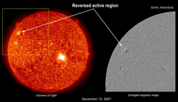 From SOHO, a UV-wavelength image of the sun and a map showing positive (white) and negative (black) magnetic polarities. The new high-latitude active region is magnetically reversed, marking it as a harbinger of a new solar cycle.